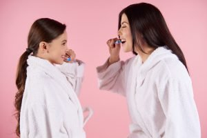 Mother and daughter in gowns brushes teeth.